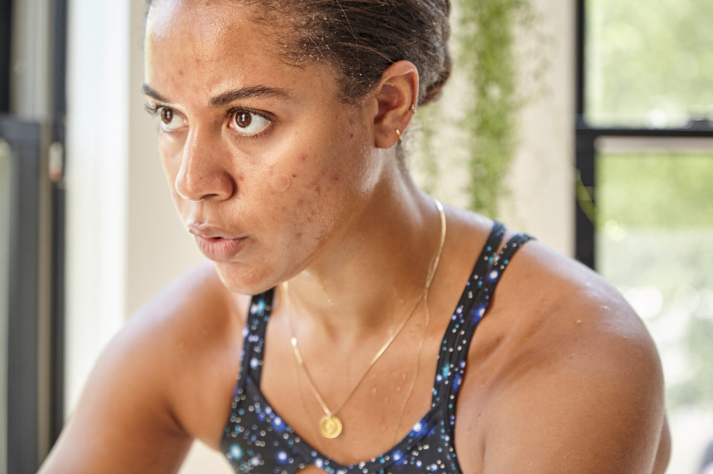 African American woman with acne sweating while working out