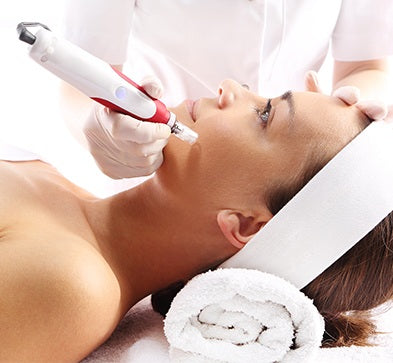Woman receiving microneedling treatment with a professional