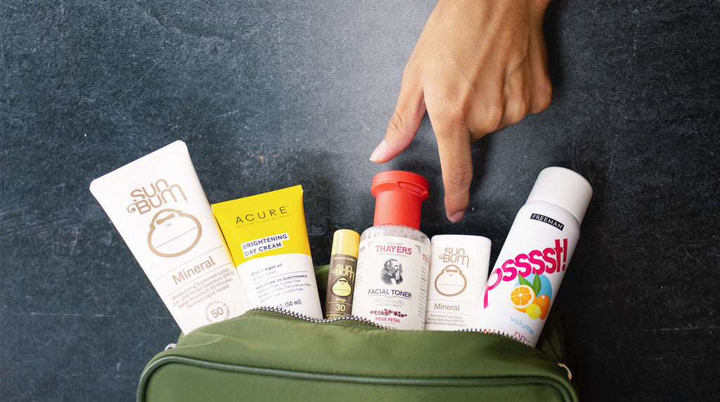 hand grabbing travel skincare products from dopp kit