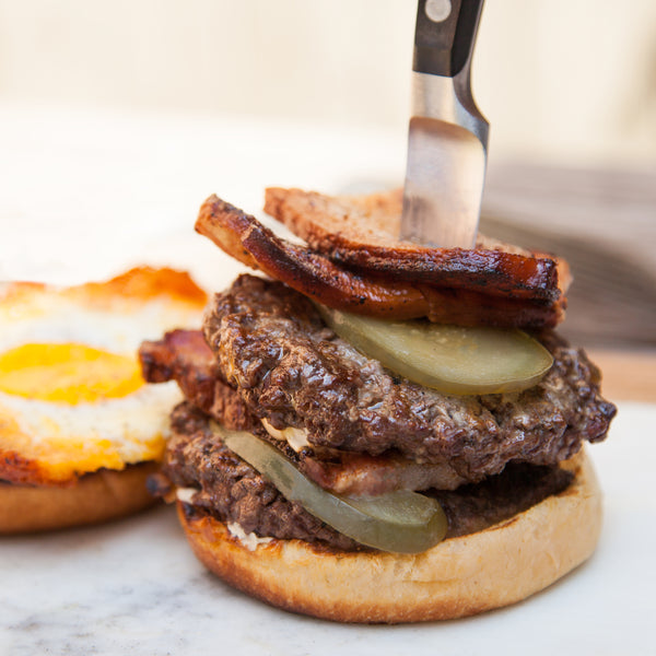 A burger with 2 patties and a knife stuck in the top with pickles and bacon.