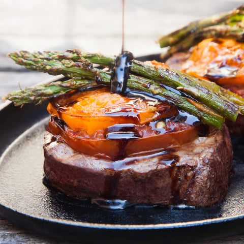 Grilled filet mignon topped with sliced tomatoes and asparagus being drizzled with balsamic reduction sauce on a cast iron skillet.