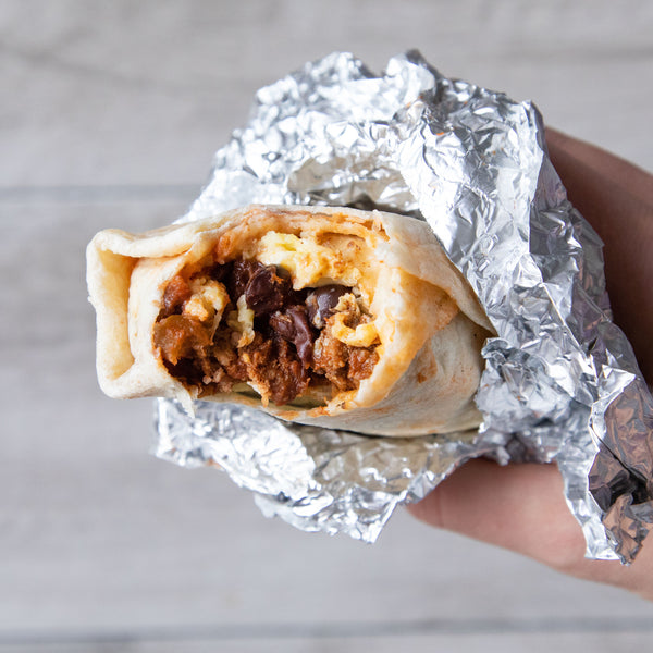 Breakfast burrito made with ground beef, eggs, and cheese. It is wrapped in foil and then folded back with a bite taken out.