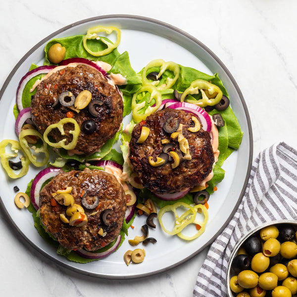 three burgers on a platter with lettuce and a Mexican burger rub