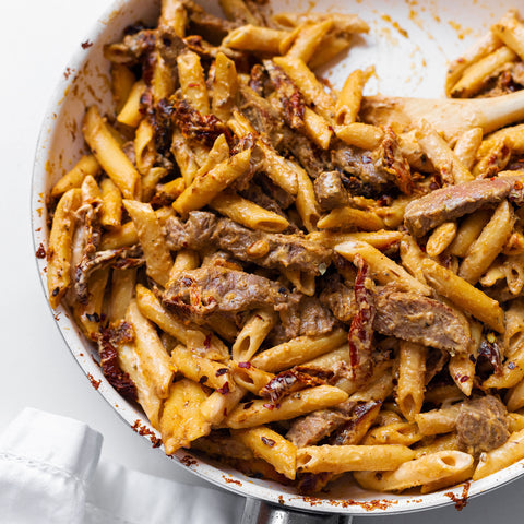 Creamy sun dried tomato and steak pasta in a white skillet