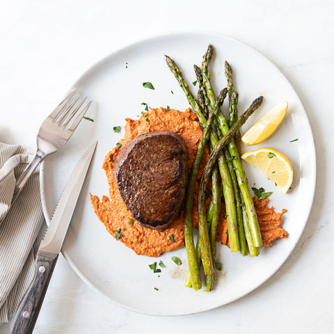 Filet mignon steak on top of romesco sauce with asparagus