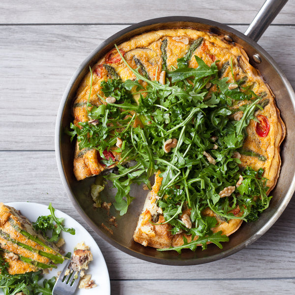 Vegetable and beef frittata in a stainless steel skillet with salad greens on top.