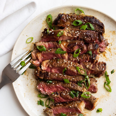 Sliced steak on a beige plate with a napkin and fork to the left.