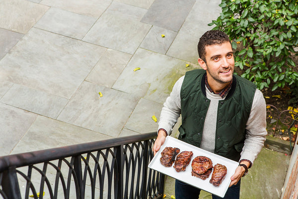 A man holding a tray of steaks on stairs