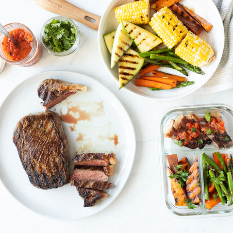 Steak with grilled vegetables and homemade salsas on a table ready to meal prep.