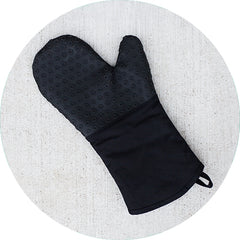 Blue oven mitt on charcoal