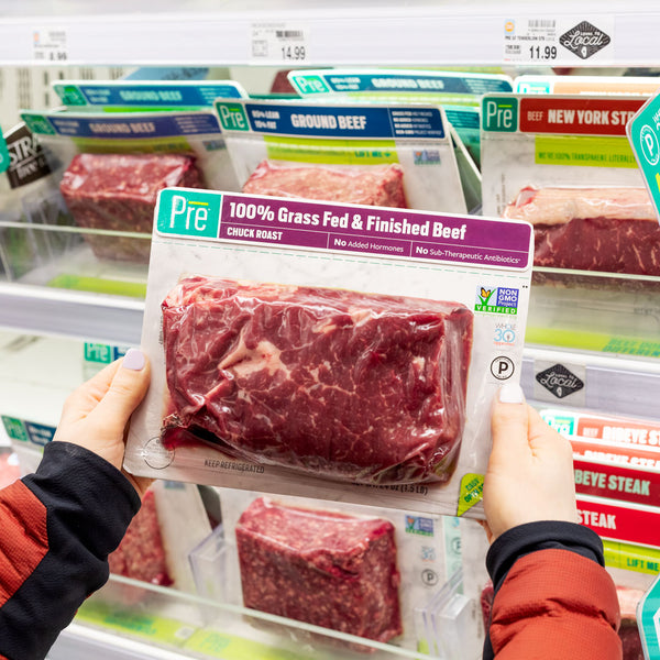 A person holding up Pre beef at a grocery store