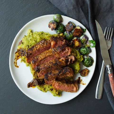 Turmeric rubbed steak on top of kale mashed potatoes and brussel sprouts.