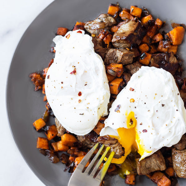 Sweet Potato and beef hash with poached eggs on top. One of the eggs is being pierced with a fork and the yolk is melting out.