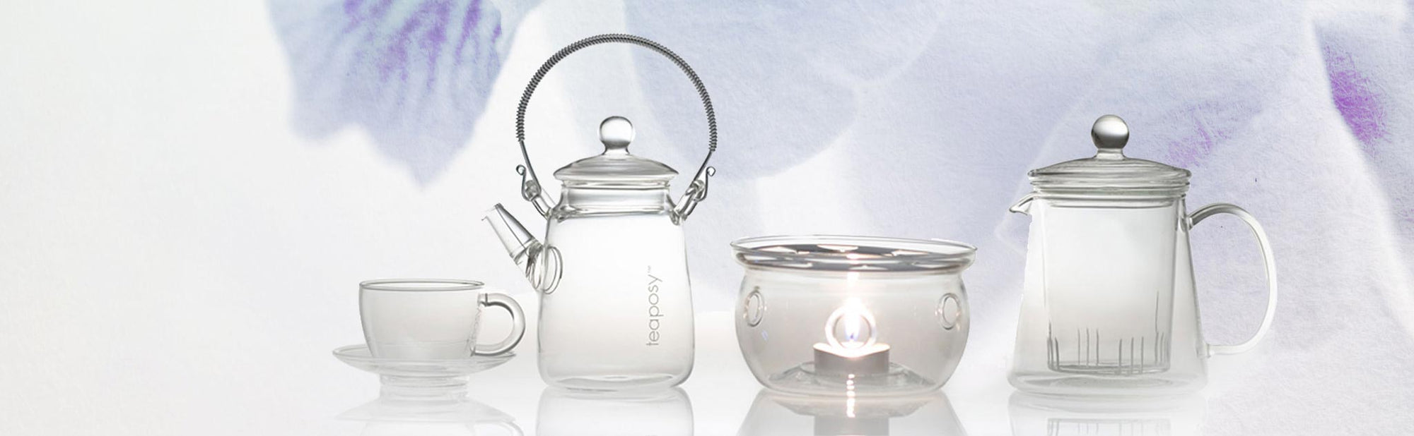 A collection of four glass teawares including two teapots one cup and saucer set, and a tea warmer