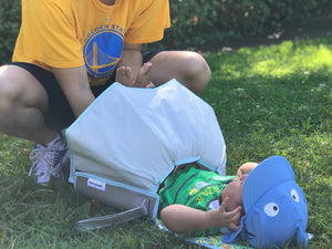 Portable Baby Diaper Changing Pad. Covers the baby's bottom so you can change your baby's diaper when there is no changing station around. Here it is being used at the park at a picnic.