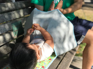 Portable Baby Diaper Changing Pad. Covers the baby's bottom so you can change your baby's diaper when there is no changing station around. Here it is being used on a park bench.
