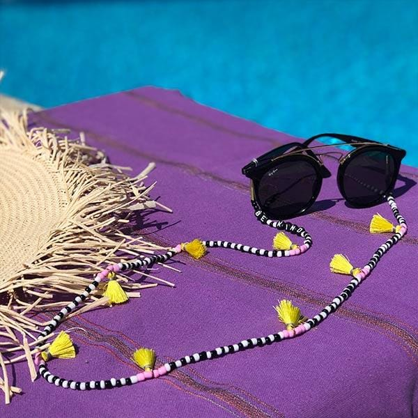 black white beaded purple tassels eyeglass chain on the beach towel