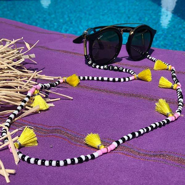 black white beaded purple tassels sunglass chain on the beach towel