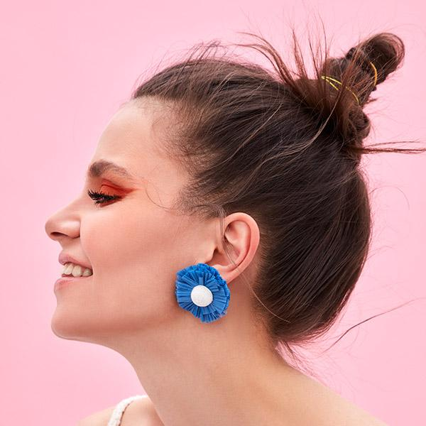 woman wears blue bloom ponponiere branded earrings on the front of pink wall