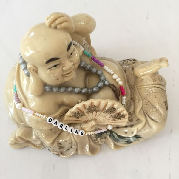 Natural pearl and beaded choker necklaces on top of Budda statue