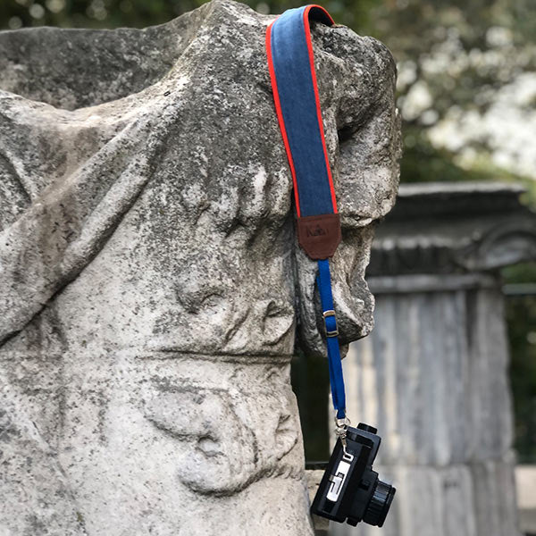 camera with handcrafted denim camera strap on top of the stone decor
