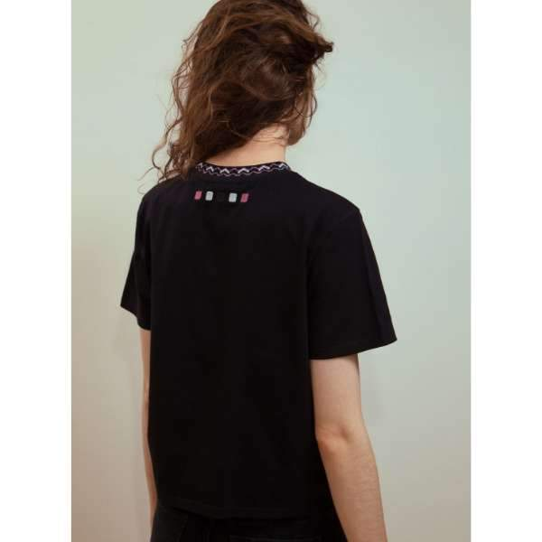 A woman with glittered jacquard ribbed black tee