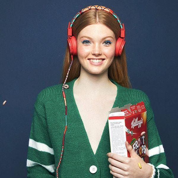 a girl in front of the blue wall wear happy-nes branded urbanears plattan 2 headphones pasific popsicle