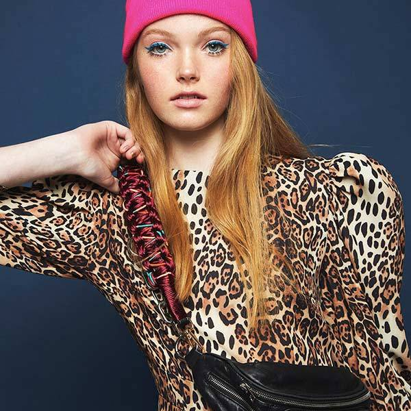 girl with orange hair in pink hat wearing leopard patterned blouse with Happy-nes bag accesorries