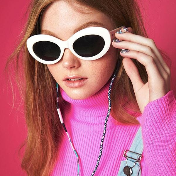 a girl in front of the maroon wall wears pink sweater and white sunglasses with colourful earphone