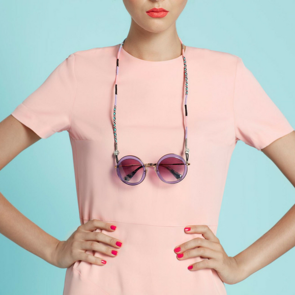 A woman who wears a pink t-shirt in front of the blue wall wears a colorful glasses strap