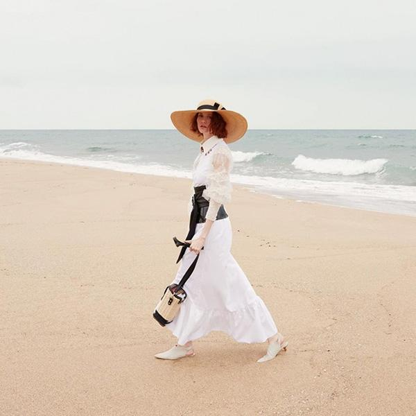A woman in the long white dress on the beach with hand wickered basket shoulder bag