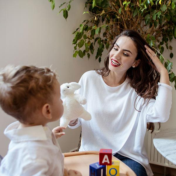 A woman with Accouchée branded white knitwear nursing sweatshirt plays with her son