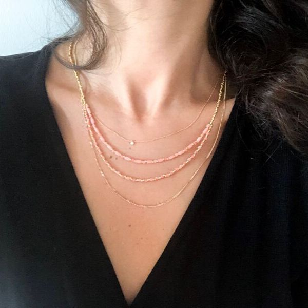 A woman in black blouse wearing bonjouk studio branded lou pink coral necklace