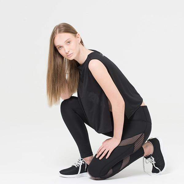 A woman with mesh panel legging and black top in front of the white wall
