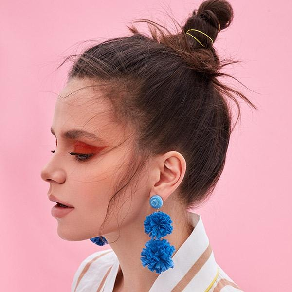 woman wears ocean blue colour silk thread and raffia pompoms detailed long earrings on the front of pink wall