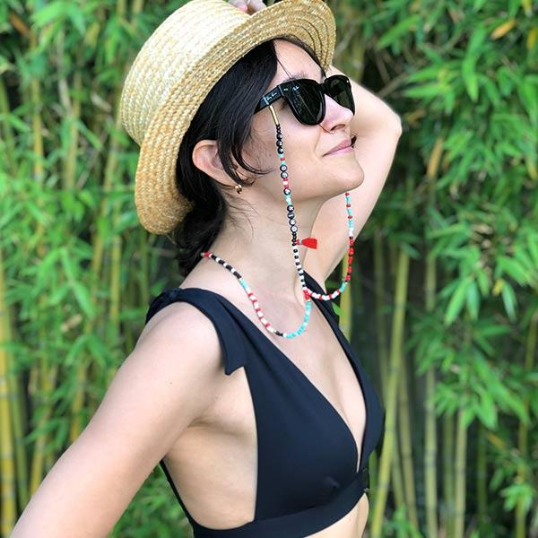 A woman with black bikini top wears colourful beaded handmade 35 inch one of a kind eyeglass chain