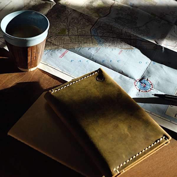 a map, coffee and passport sleeve on the table