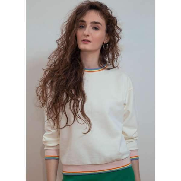 A woman with rainbow jacquard ribbed white sweatshirt