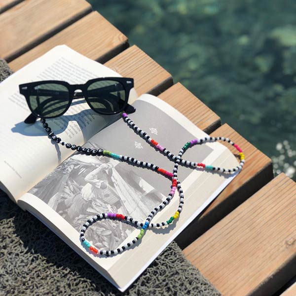 Colourful beaded eyeglass chain displayed on a dock