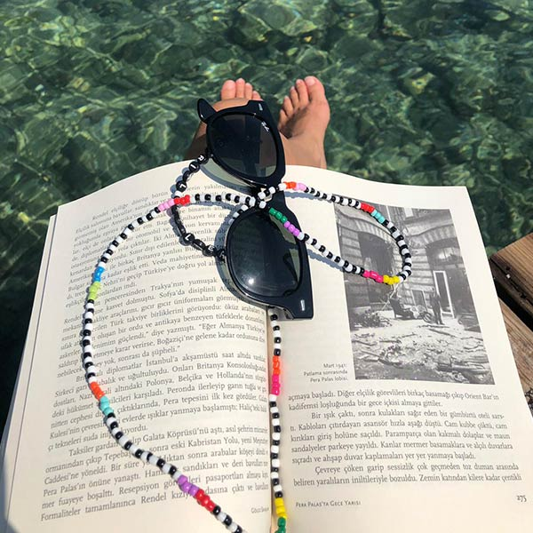 Colourful beaded eyeglass chain on a book with a sea view