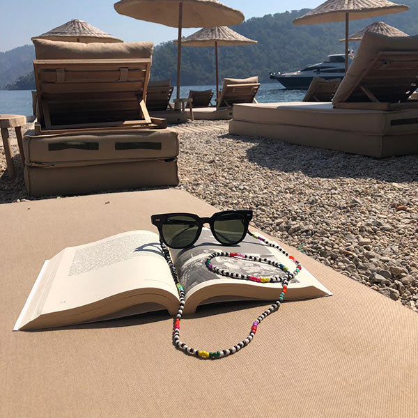 Colourful beaded eyeglass chain displaying at a beach