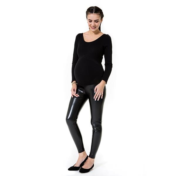 A pregnant woman wears shiny black high rise maternity legging