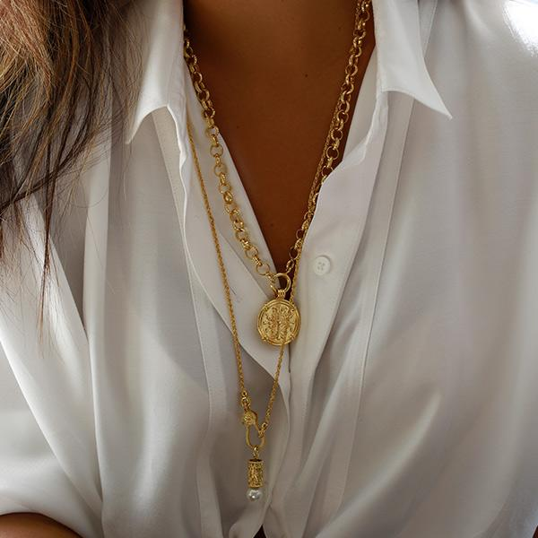 A woman with black shirt layered gold chains