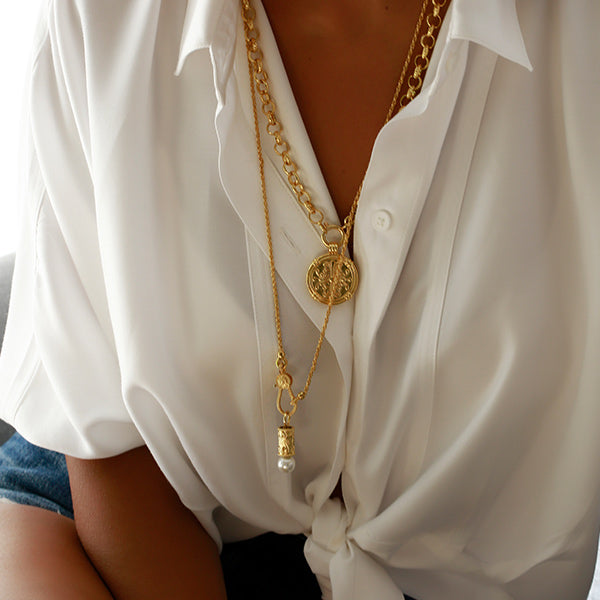 A woman with white shirt layered gold chains