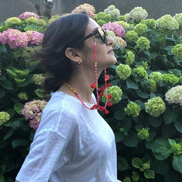 A woman with colourful beaded handmade 35 inch strawberry lemonade sunglass chain