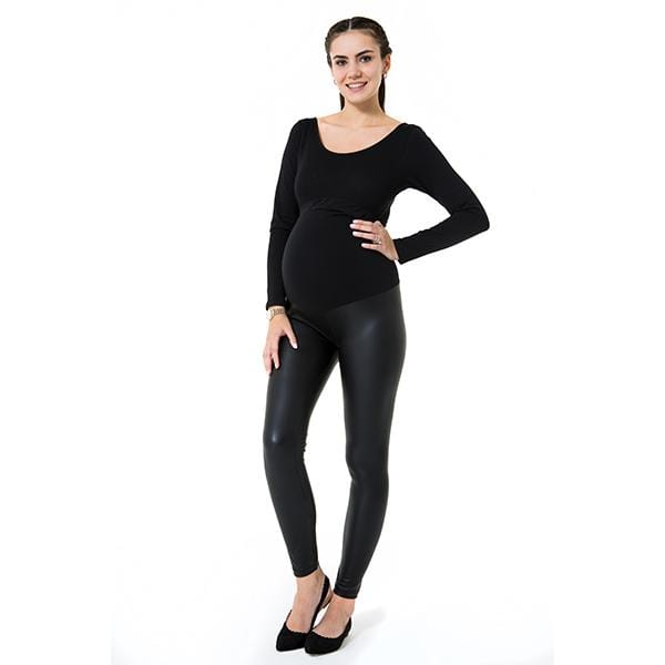 A pregnant woman wears subtle high black high rise maternity legging