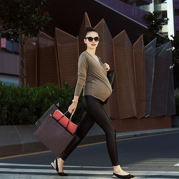 A pregnant woman with subtle low rise maternity legging walks in the street