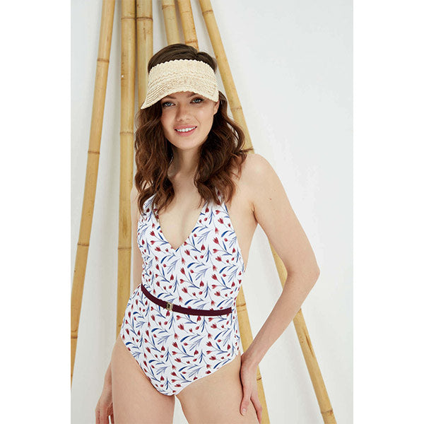 A woman with straw hat wears floral pattern burgundy arched swimsuit