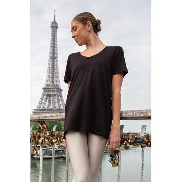 ballerina dancing with beige leggings and black V-neck t-shirt in front of effiel tower in paris