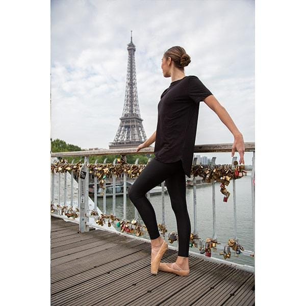 ballerina dancing with beige leggings and black mock neck t-shirt in front of Eiffel tower in Paris